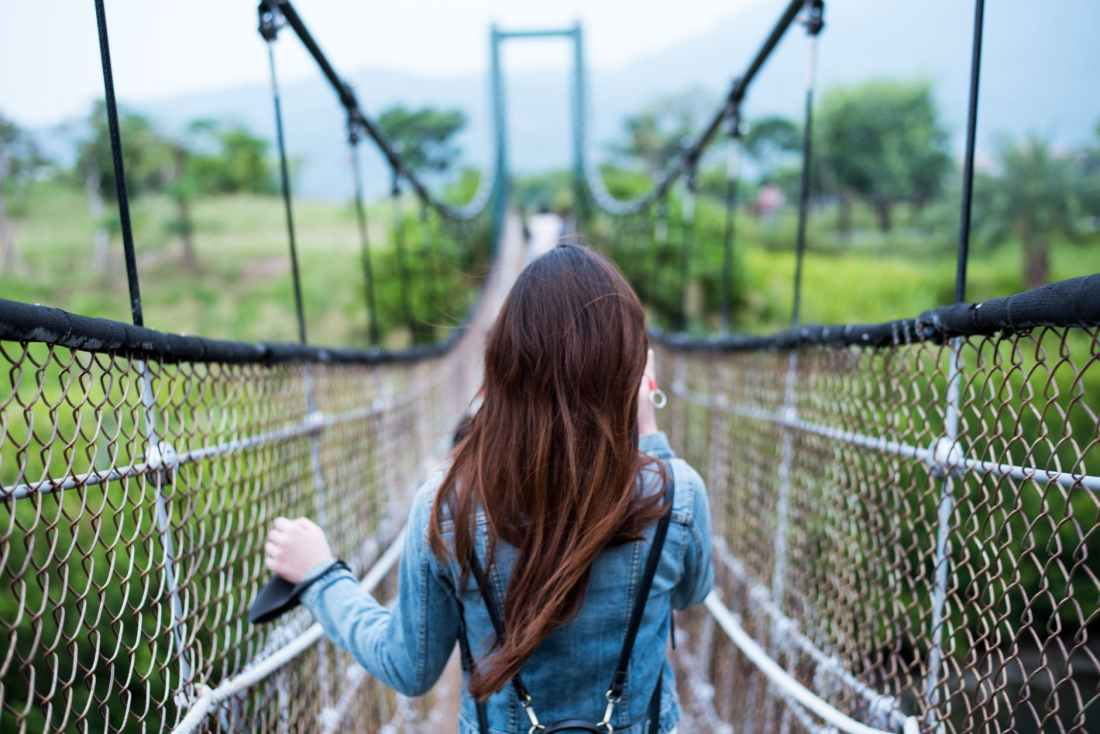 woman in blue long sleeved dress on rope bridge