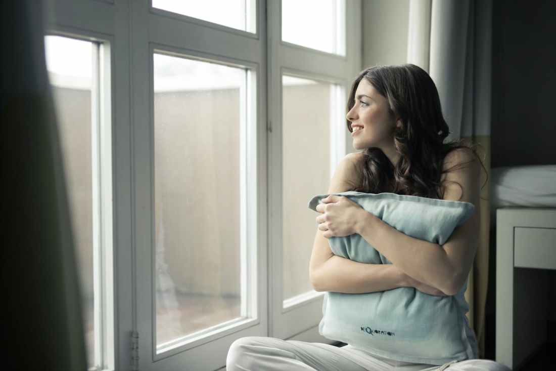 black haired woman hugging gray pillow near glass panel window