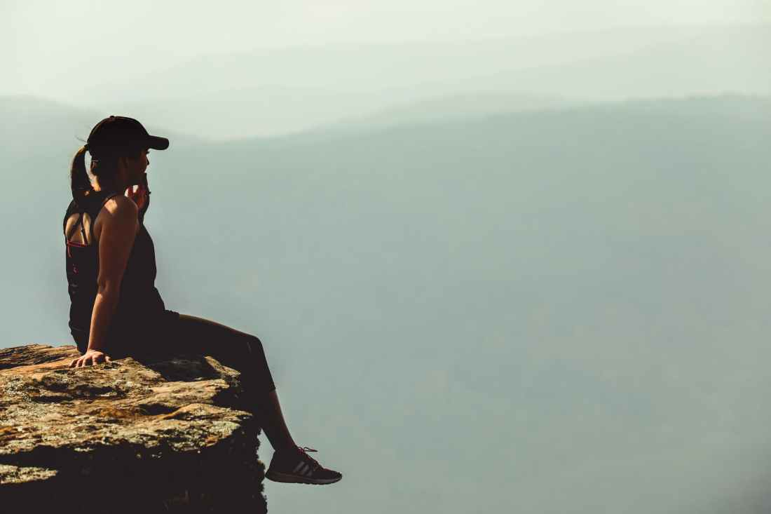 woman sitting on cliff